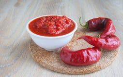 Tomatensauce in einem weißen Behälter und heißen einem Pfeffer des roten Paprikas Lizenzfreie Stockfotografie