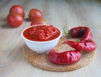 Tomatensauce in einem weißen Behälter und heißer ein Pfeffer und Tomaten des roten Paprikas Lizenzfreie Stockfotografie