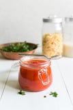 Tomatensauce im Glas auf weißem Holztisch Stockbilder