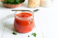 Tomatensauce im Glas auf weißem Holztisch Lizenzfreie Stockfotos
