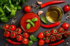 Tomatensauce mit Basilikum auf schwarzem Hintergrund Stockbild