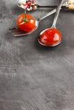 Tomatensaus, kers, kruiden in vork en lepels op een donkere backgr Royalty-vrije Stock Foto
