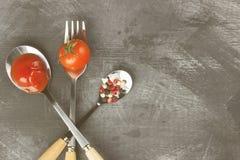 Tomatensaus, kers, kruiden in vork en lepels op een donkere backgr Stock Afbeelding