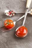 Tomatensaus, kers, kruiden in vork en lepels op een donkere backgr Stock Fotografie