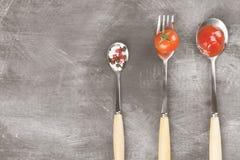 Tomatensaus, kers, kruiden in vork en lepels op een donkere backgr Stock Foto