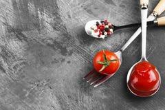 Tomatensaus, kers, kruiden in vork en lepels op een donkere backgr Stock Foto's