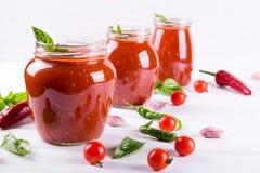 Tomatensaus, ketchup in glaskruik en ingrediënten stock afbeelding