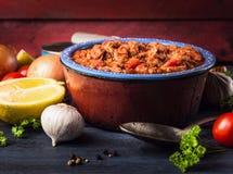 Tomatensaus met tonijnvissen in oude pot met lepel en kruiden Stock Foto's