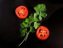 Tomatenscheiben und Zweige der Petersilie Lizenzfreies Stockbild