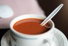 Tomatensuppe im Becher mit Löffel und Platte und Gewürze von einem Winkel Stockbild
