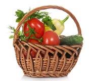 Tomater, gurkor, peppar och gräsplaner i korg royaltyfri foto