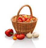 Tomater i korg, lök och peppar på stubbe i trädgård Arkivbilder