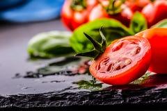 Tomater Körsbärsröda tomater Coctailtomater Ny druvatomatkaraff med olivolja på tabellen tonat foto royaltyfri fotografi