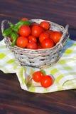 Tomater med basilika i korg Royaltyfria Foton
