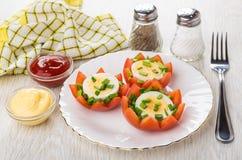 Tomater med kokta ägg och löken, bröd som är salt, peppar, såser Arkivbild