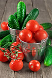 Tomater och gurkor i hinkar Arkivfoto