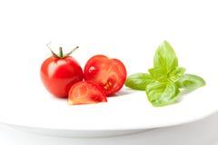 Tomater och ny basilika på den vita plattan Royaltyfri Foto