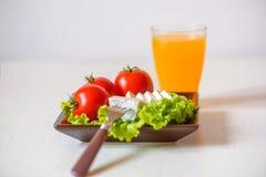 Tomater och ostskivor ligger på ett ark av ny sallad i en platta Ett exponeringsglas av orange fruktsaft står på tabellen Arkivbild