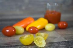 Tomater och peppar på trä Arkivbild