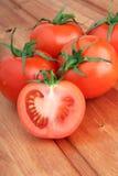 Tomater och skiva av tomaten på träbakgrund Fotografering för Bildbyråer
