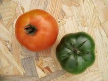 Tomater på en tabell färgar i motsats gräsplan och rött royaltyfria foton