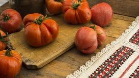 Tomater på lantlig träskärbräda och trätabellen Royaltyfri Foto