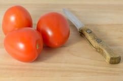 Tomater på skärbrädan och en kniv Arkivfoto