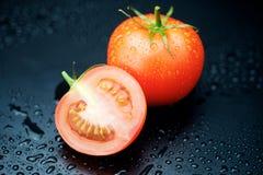 Tomater på svart bakgrund Arkivfoto
