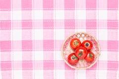 Tomater på tabellen och som sätter det i en korg Royaltyfri Foto