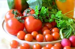 Tomater, rädisor, peppar och persilja på träskärbräda Arkivbilder