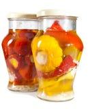 Tomates adobados, calabazas rellenos y del arbusto y tuétanos vegetales en un tarro de cristal. Aún-vida en un fondo blanco Fotografía de archivo libre de regalías