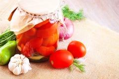 Tomates adobados en tarros con las especias y las verduras en una tabla Imagen de archivo libre de regalías