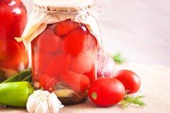 Tomates adobados en tarros con las especias y las verduras en una tabla Foto de archivo