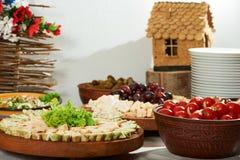 Tomates adobados, rollos vegetales, uva del platewith del queso Imagen de archivo libre de regalías