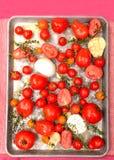 Tomates, ajo, cebollas y tomillo frescos en cacerola de la asación Foto de archivo libre de regalías