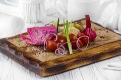 Tomates, ajo y cebolla Diversas verduras frescas y conservadas en vinagre en un tablero foto de archivo libre de regalías