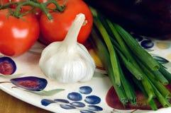 Tomates, ajo y scallions en una placa. Fotografía de archivo