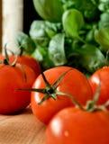 Tomates, albahaca y una botella de vino Imagenes de archivo