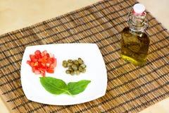 Tomates, alcaparras y albahaca en una placa y un aceite de oliva blancos Fotos de archivo