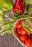 Tomates, alface, pimenta doce em uma placa de madeira rustic Foto de Stock