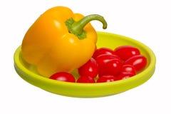 Tomates amarillos de la pimienta y de cereza en una placa verde Fotos de archivo libres de regalías