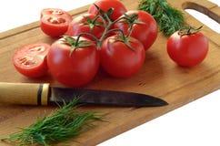 Tomates, aneto e faca velha em uma placa de corte em um backg branco Imagens de Stock
