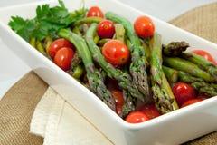 Tomates asados del espárrago y de cereza Foto de archivo