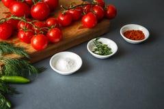 Tomates avec des pappers et des herbes verts Photographie stock