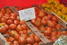 Tomates avec le prix à payer sur le marché végétal Photographie stock libre de droits