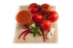 Tomates avec le verre de jus d'isolement sur le fond blanc Photo libre de droits