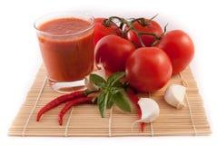 Tomates avec le verre de jus d'isolement sur le fond blanc Photos stock