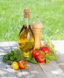 Tomates, botella del aceite de oliva, coctelera de la pimienta e hierbas maduros frescos Imagen de archivo libre de regalías