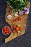 Tomates, cebola, alho, salsa e pimentão frescos na placa de madeira Foto de Stock Royalty Free