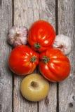 Tomates, cebola e alho na tabela Imagem de Stock Royalty Free